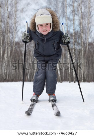 Young boy stands on cross-country skis and leans on poles inside winter forest at sunny day - stock photo