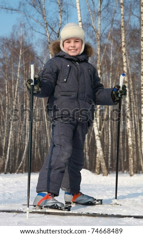 Young boy stands on cross-country skis inside winter forest at sunny day - stock photo