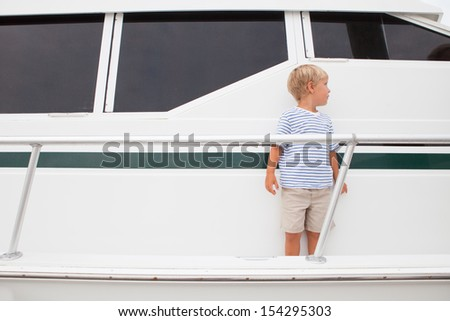 Young boy stands on edge of large yacht