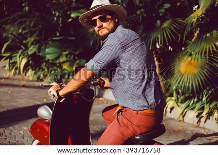 young boy straw hat shirt, red trousers posing on a red vintage scooter, Vespa scooter, bike stylish, handsome guy in sunglasses, outdoor portrait, close up, bali, indonesia - stock photo