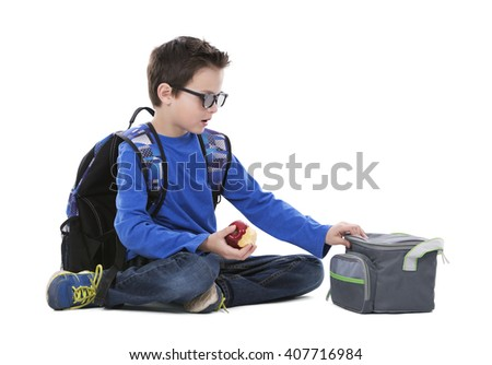 young boy student with backpack and apple in his hand on white background - stock photo