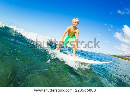 Young Boy Surfing Ocean Wave - stock photo