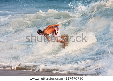 Young boy surfing on the wave - stock photo