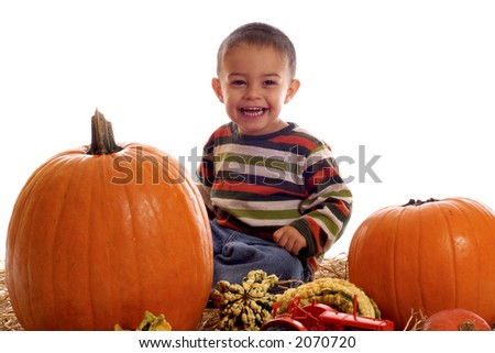 Young boy surrounded by pumpkins and gourds.  Isolated on white.