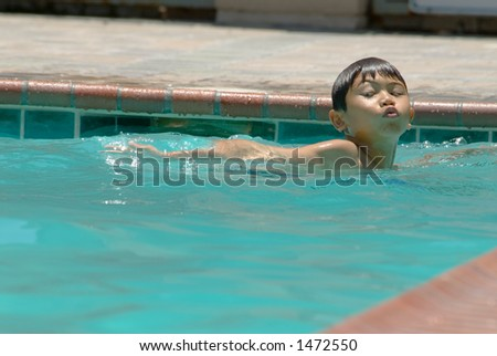 Young boy swimming in a pool
