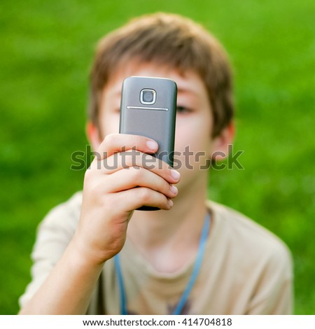Young boy taking a picture with smart phone