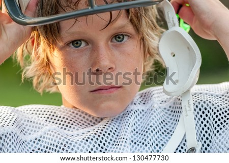 Young boy taking his football helmet off after a game - stock photo