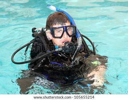 Young boy taking scuba diving lessons in pool.