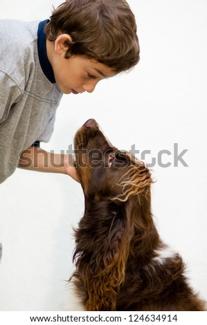 young boy talking to his pet dog against a white background