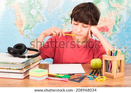 Young boy thinking about his homework - stock photo