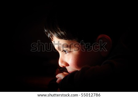 young boy thinking looking into light - stock photo