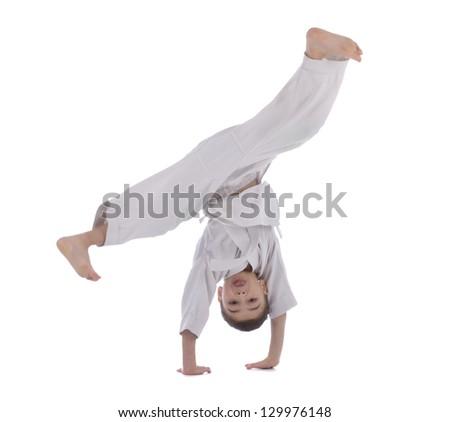 Young boy training acrobatic in kimono isolated on white background - stock photo
