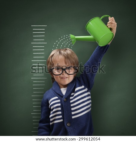 Young boy trying to make himself taller with watering can measuring his growth in height against a blackboard scale - stock photo