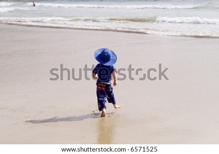 Young boy, two years old, playing at the beach at the water's edge