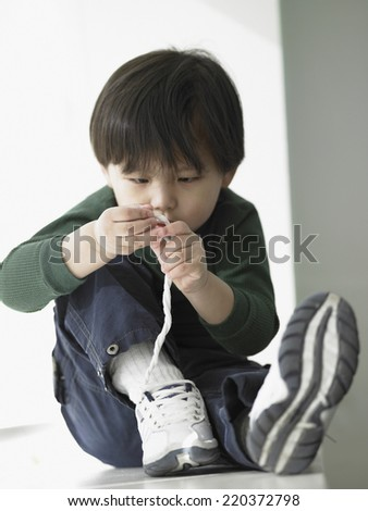 Young boy tying shoelaces - stock photo