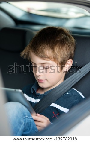 Young boy using a tablet computer while sitting in the back passenger seat of a car with a safety belt over his shoulder - stock photo