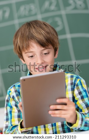 Young boy using a tablet in the schoolroom and smiling as he navigates the internet while standing in front of the blackboard - stock photo