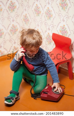 Young boy using red phone with rotary dial