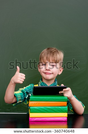 Young boy using tablet computer and showing thumbs up