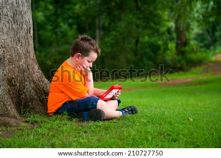 Young boy using tablet computer outdoors at park - stock photo
