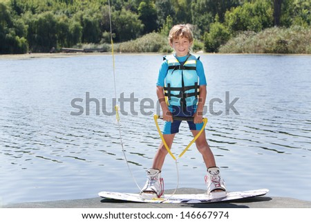 young boy wakeboarding - stock photo