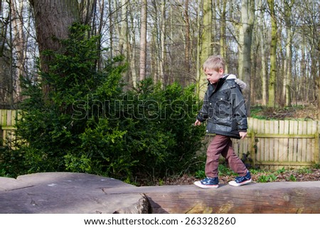 Young boy walking along a wooden beam - stock photo