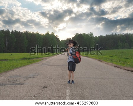 Young boy walking on a countryside road. traveler concept