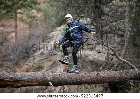 young boy walking on a fallen tree