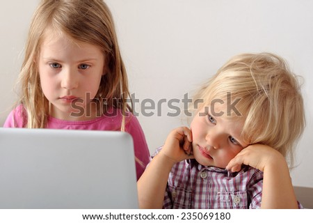 Young boy watches his sister playing a computer game on a laptop. He wishes he could play. Focus on boy. Short depth of field - stock photo