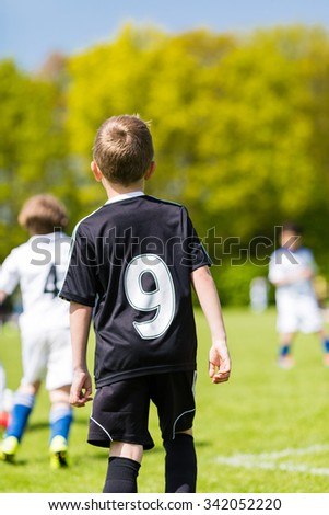 Young boy watching his team mates play a kids soccer match on soccer field with green grass.