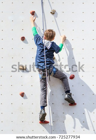 Young boy way up on a white climbing wall