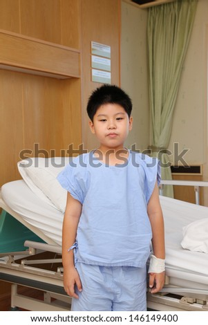 Young boy wear patient suit standing  in front of hospital bed - stock photo