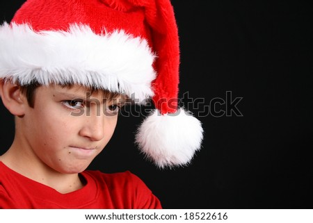 Young boy wearing a red shirt and christmas hat
