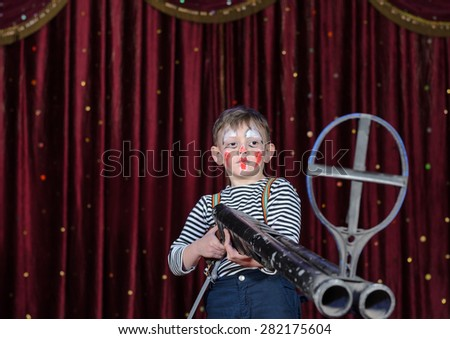 Young Boy Wearing Clown Make Up Standing on Stage Aiming Large Prop Shot Gun Rifle in front of Red Curtain - stock photo