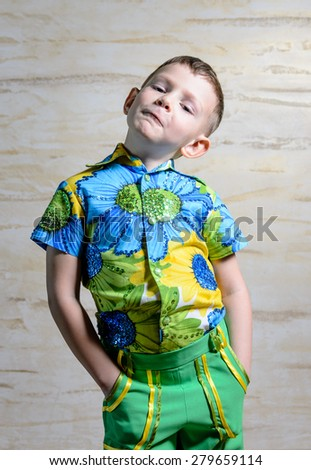 Young Boy Wearing Colorful Floral Print Shirt Standing with Hands on Hips in Studio with Patterned Background, Looking Disapprovingly at Camera - stock photo