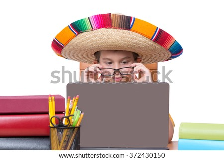 Young Boy Wearing Eyeglasses and Colorful Mexican Sombrero Hat Looking Down at Laptop Computer Screen While Sitting at Desk Surrounded by Colorful Books and Binders and Writing Supplies - stock photo