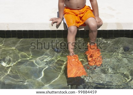 Young boy wearing flippers in a swimming pool