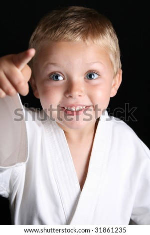 Young boy wearing his karate uniform on a black background - stock photo