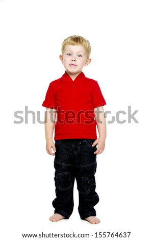 Young boy wearing jeans and a red T-shirt stood isolated on a white background looking into the camera