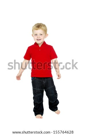 Young boy wearing jeans and a red T-shirt stood isolated on a white background running towards the camera
