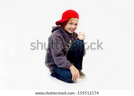 Young boy wearing red baseball cap and holding on to baseball - stock photo