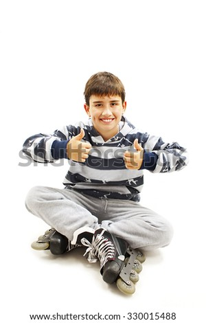 Young boy wearing roller skates sitting on floor, showing ok sign. Isolated on white background - stock photo