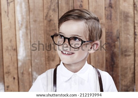 Young boy wearing spectacles, looking away  - stock photo