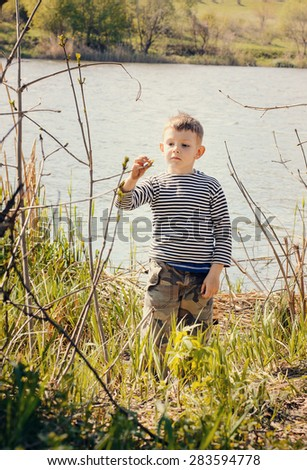 Young Boy Wearing Striped Shirt Stopping to Smell and Examine Plant Growing Amongst Reeds Along Shore of Lake - stock photo