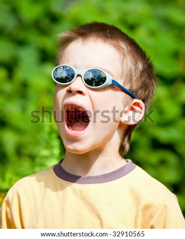 Young boy wearing  sunglasses open-mouthed with  surprise
