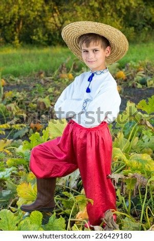 Young boy wearing traditional Ukraine clothes in wheat and poppy field on summer day outdoors background - stock photo