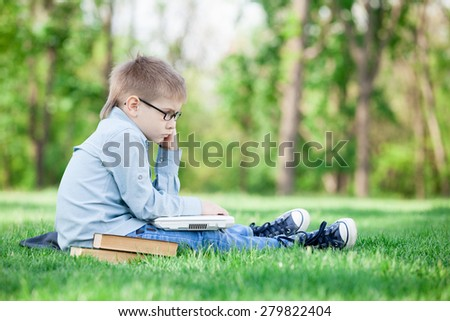 young boy with a book and laptop computer on green grass in the park - stock photo