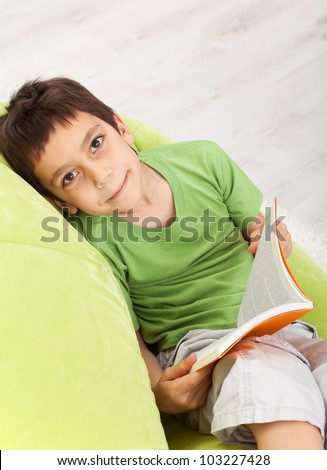 Young boy with a book - sitting on soft armchair - stock photo