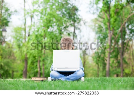 young boy with a books and laptop computer on green grass in the park - stock photo