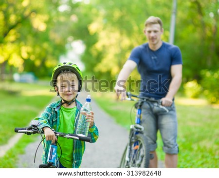 young boy with a bottle of water is learning to ride a bike with his father - stock photo